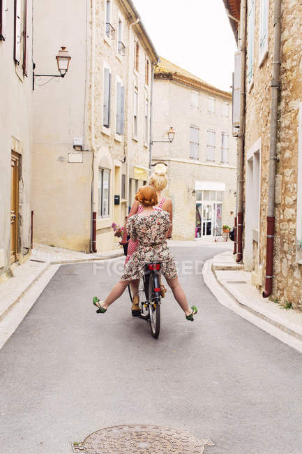 Two women riding bicycle together, differential focus — Stock Photo