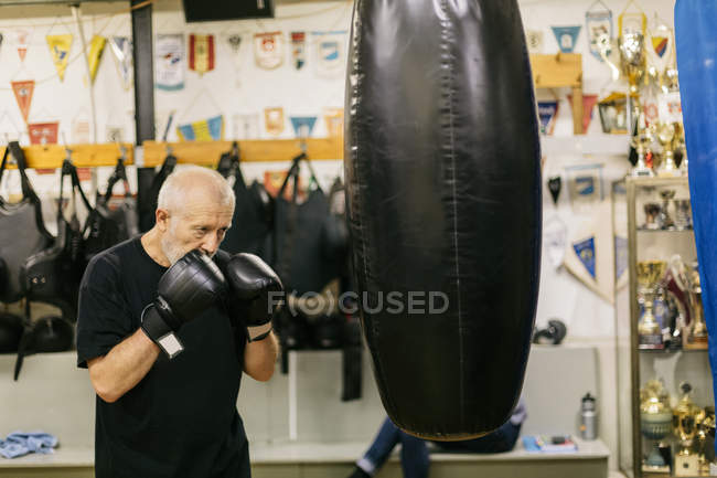 Senior man at boxing training, focus on foreground — Stock Photo