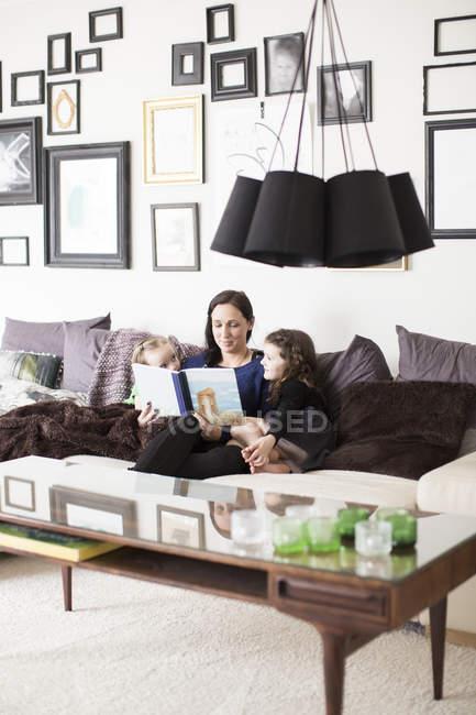 Мама читает дочерей, избирательный фокус — стоковое фото