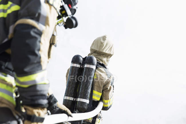 Two firefighters with oxygen tanks holding hose — Stock Photo