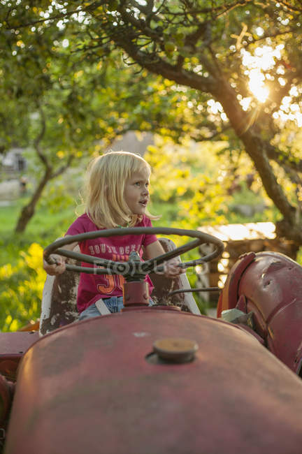 Girl on tractor looking away, lens flare — Stock Photo