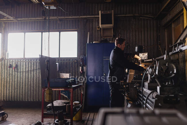Young man working in workshop, differential focus — Stock Photo
