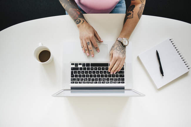 Erhöhter Blick auf tätowierte Frau mit Laptop — Stockfoto