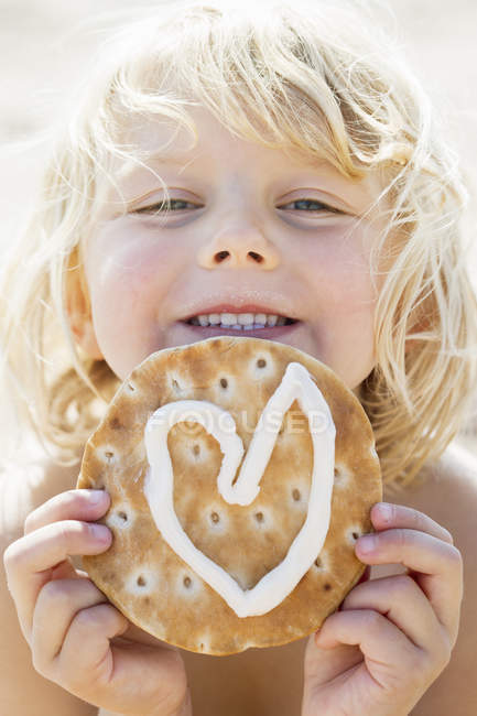 Young girl holding pastry with heart shaped icing — Stock Photo