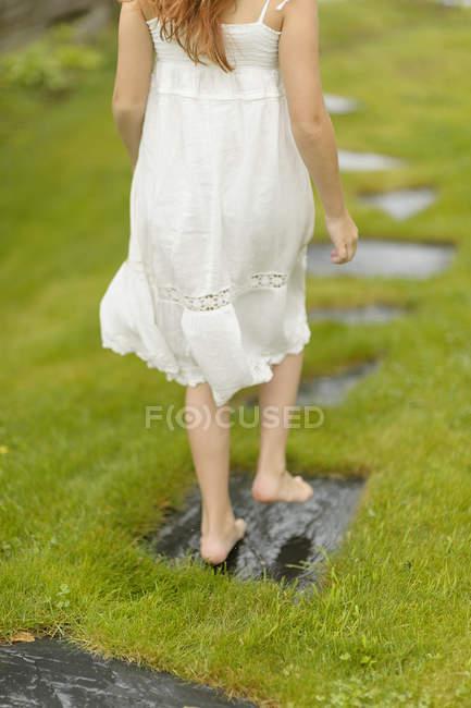 Mädchen in weißem Kleid geht Fußweg entlang — Stockfoto