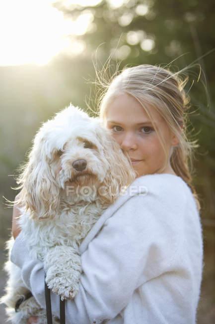Девушка держит собаку и смотрит в камеру, дифференциальный фокус — стоковое фото