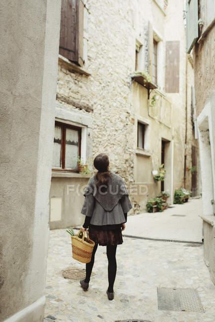 Vue arrière de la jeune femme qui marche dans la vieille ville — Photo de stock