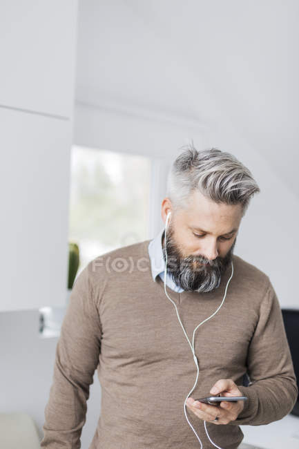 Uomo con auricolari in ascolto di smartphone, messa a fuoco selettiva — Foto stock