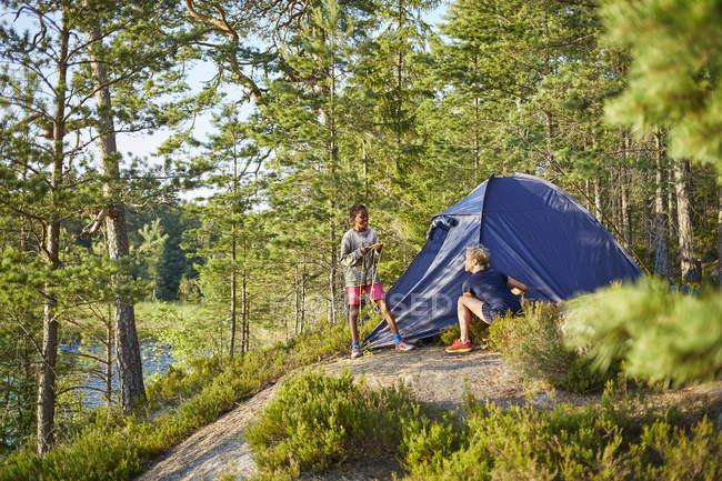 Menino e mulher acampando na floresta, foco seletivo — Fotografia de Stock