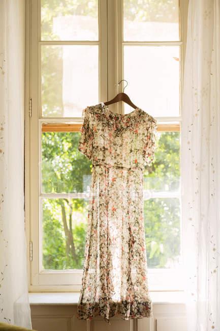 Сукня з квітковим візерунком, висить у вікно — стокове фото