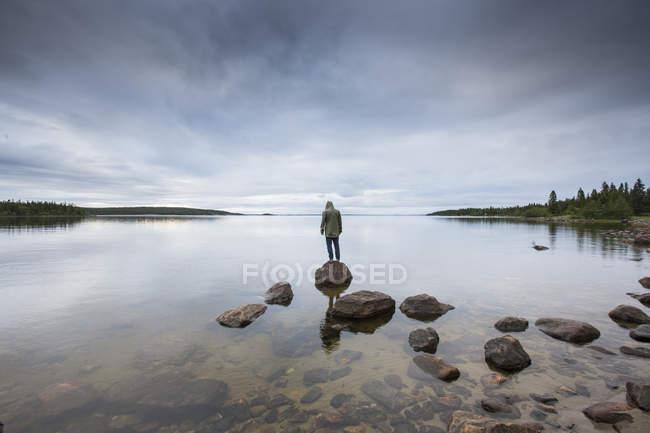Uomo in piedi sulla formazione rocciosa vicino al lago — Foto stock