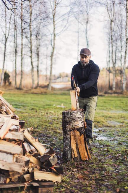Homme à la casquette de baseball, fendre le bois de feu — Photo de stock