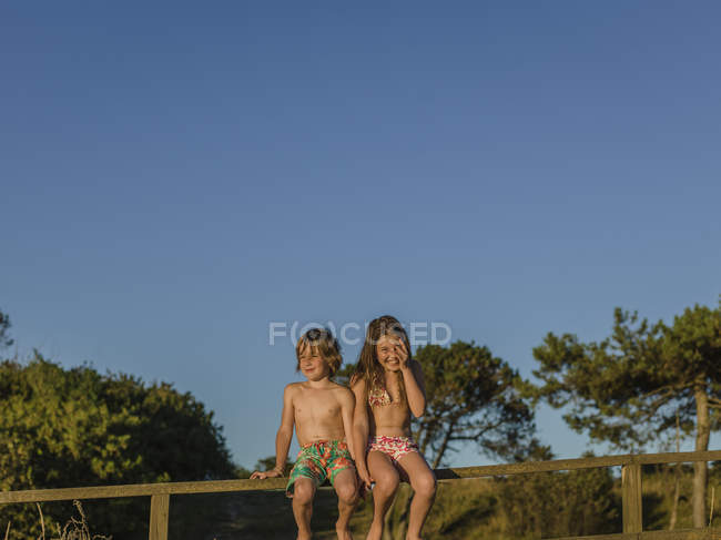 Young boy and girl sitting on fence at summer — Stock Photo
