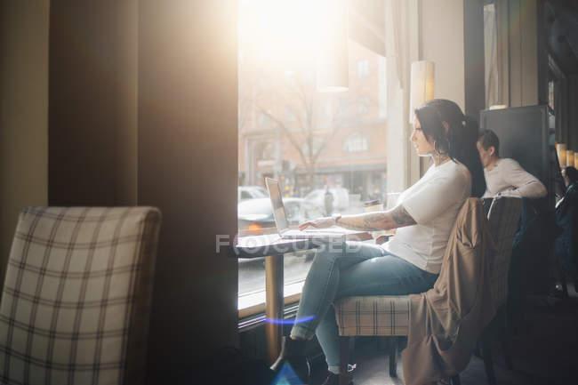 Donna che utilizza il computer portatile in caffè, messa a fuoco selettiva — Foto stock