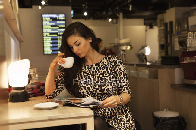 Young woman at train station drinking coffee and reading magazine — Fotografia de Stock