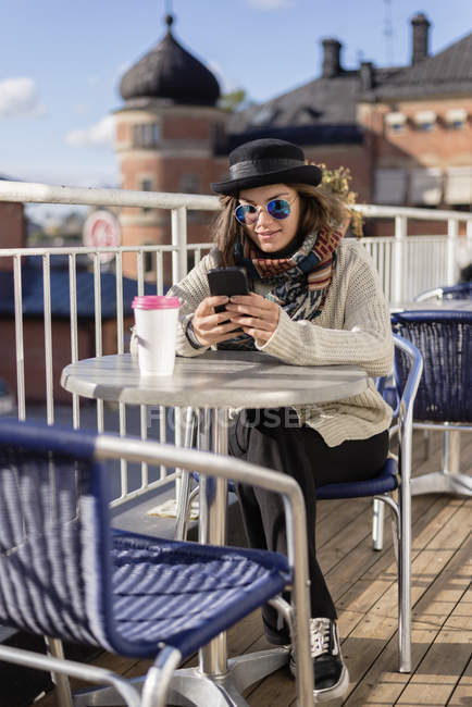 Young woman using smart phone while sitting at table — Stock Photo