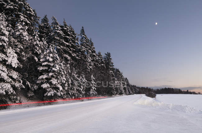 Scenic view of light trail on winter road — Stock Photo