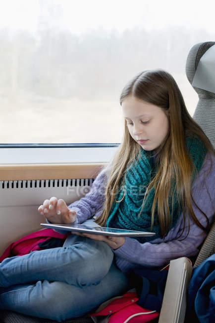 Девушка в поезде играет на цифровом планшете, избирательный фокус — стоковое фото