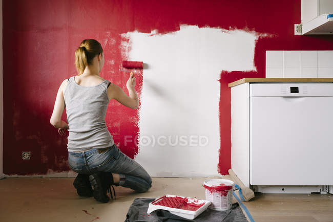 Rear view of woman painting wall in kitchen — Stock Photo