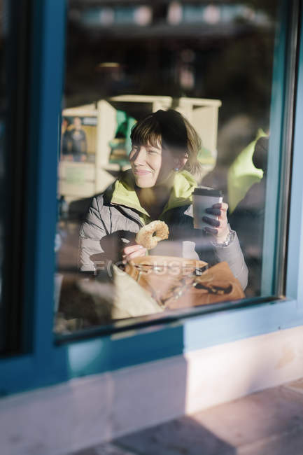 Woman in cafe seeing through window, differential focus — Stock Photo