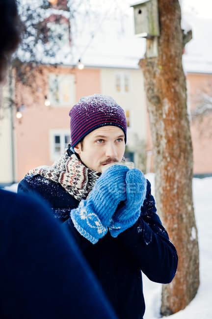 Uomo che beve cioccolata calda all'aperto in inverno — Foto stock