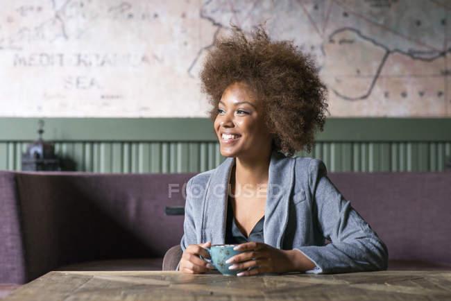 Giovane donna sorridente in caffetteria con la tazza di caffè — Foto stock