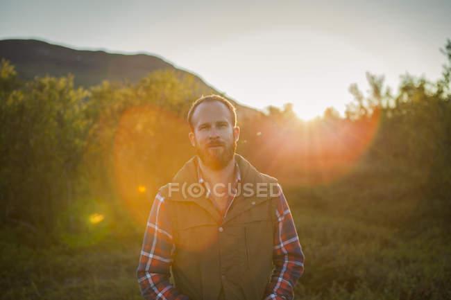 Человек в сельской местности с блики, фокус на переднем плане — стоковое фото