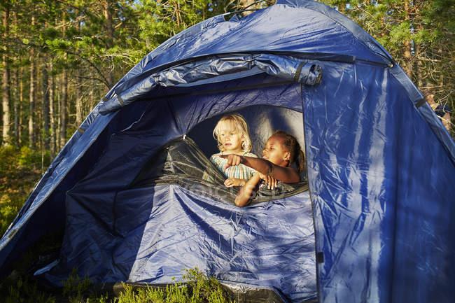 Filles dans une tente bleue, la forêt de se concentrer sur le premier plan — Photo de stock