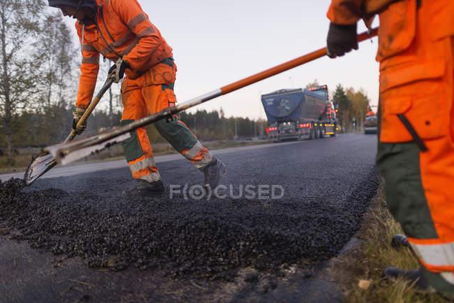 Manual workers repairing road, selective focus — Stock Photo