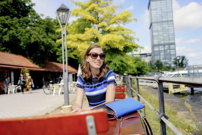 Mulher sorridente na mesa de café, foco diferencial — Fotografia de Stock