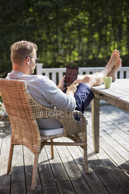 Man using digital tablet outdoors, focus on foreground — Stock Photo
