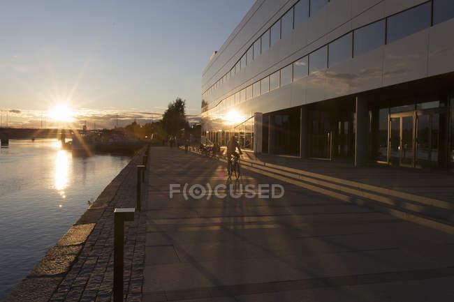 Acera por edificio exterior y sol reflejando en el río - foto de stock