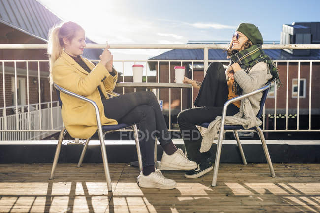 Two young women using smart phone while sitting at table and drinking coffee — Stock Photo
