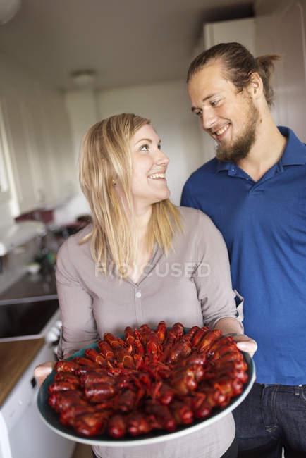 Мужчина и женщина, держащие раков на тарелке, сосредотачивайтесь на переднем плане — стоковое фото
