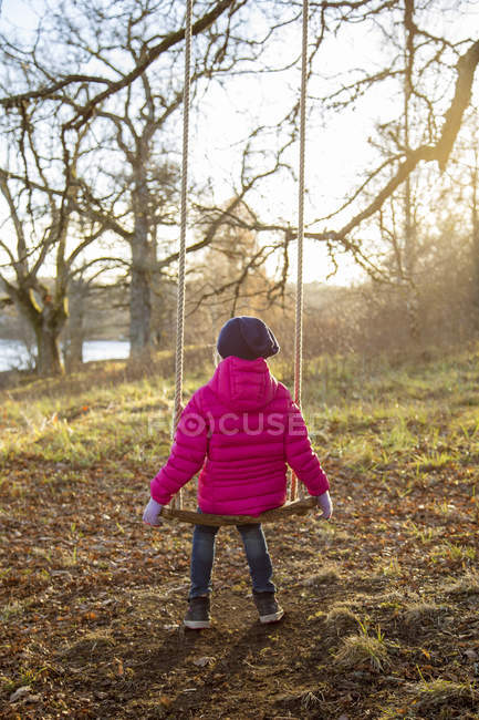 Rear view of girl in pink jacket looking at river — Stock Photo