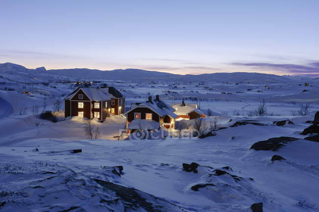 Illuminated buildings in snow at winter — Stock Photo