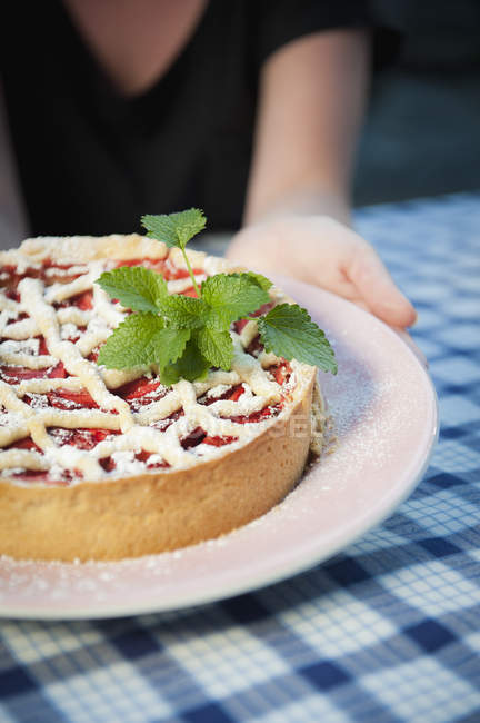 Cropped view woman with strawberry pie in icing sugar with mint leaves — Photo de stock