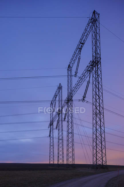 Scenic view of electric wires in field at sunset — стокове фото