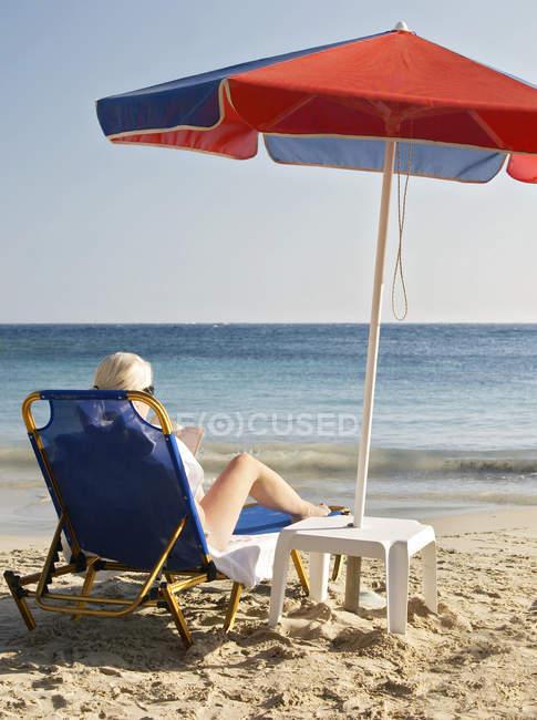 Жінку загоряти і читання книги на пляжі — стокове фото