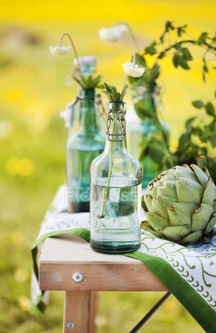Цветы в бутылки и артишок на столе, выборочный фокус — стоковое фото