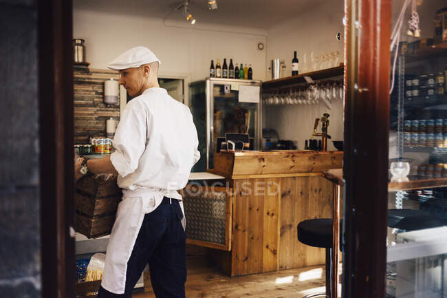 Butcher carrying crate at butcher shop — Stock Photo