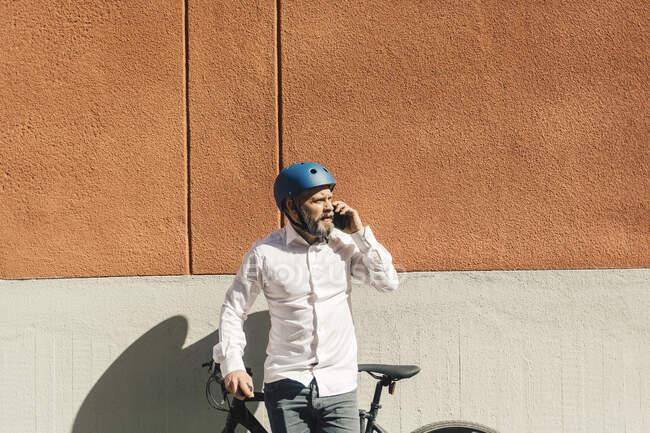 Uomo in piedi con la bicicletta e parlare su smartphone — Foto stock