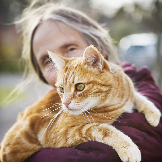 Woman carrying cat, focus on foreground — Stock Photo