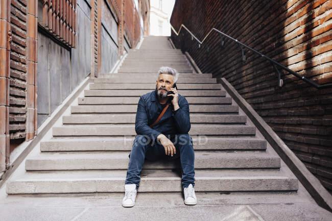 Человек со смартфоном, сидящий на лестнице — стоковое фото