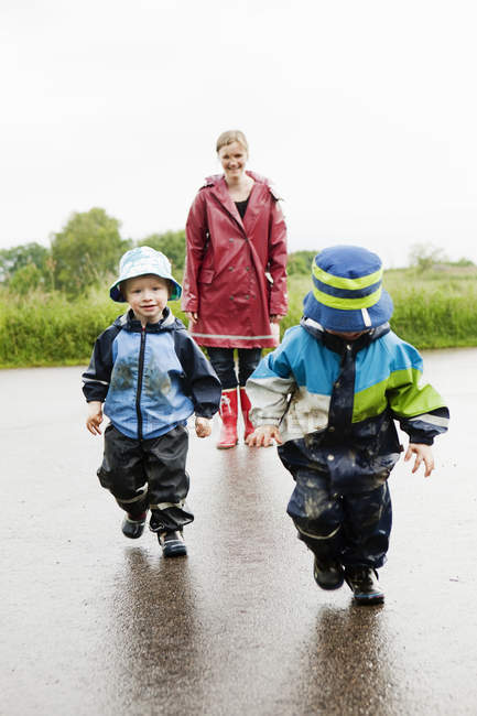 Mother and children walking on wet road — Stock Photo