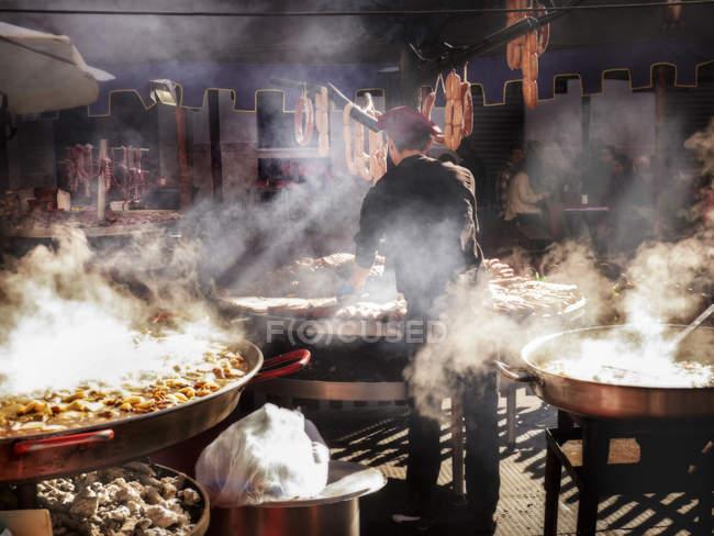 Людина, що приготування їжі на ринку малюків Сантс — стокове фото