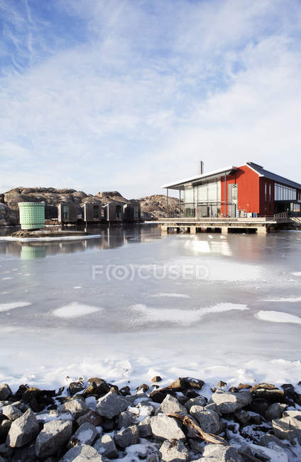 Red wooden house by frozen sea — Stock Photo