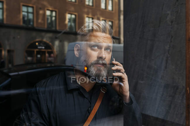 Homem em telefone inteligente através da janela — Fotografia de Stock
