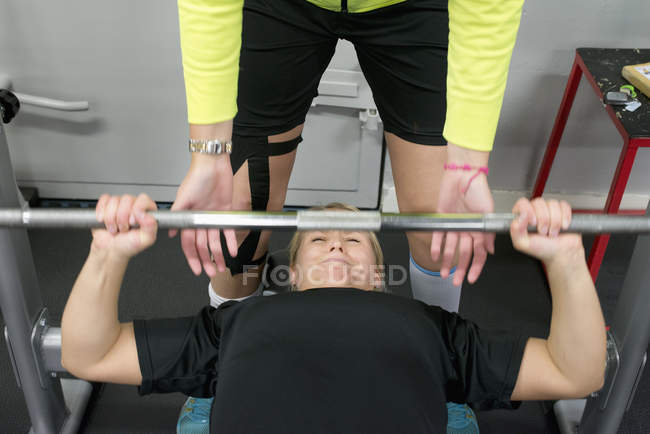 Young woman weight lifting with barbell in gym, selective focus — Foto stock