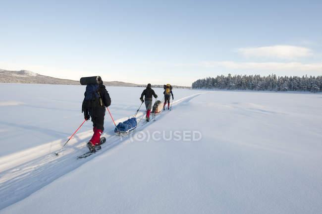 Three men cross-country skiing across frozen lake in winter — стоковое фото